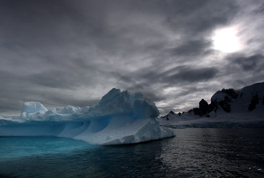 A blue iceberg under a cloudy sky.