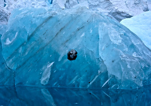 A rock embedded in an iceberg.