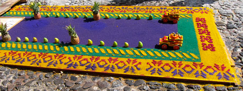 A carpet made of colored saw dust in a street in Antigua.