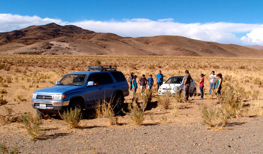 Blue tows a car out of the desert.