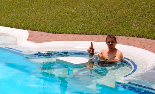 Kobus takes a dip in the pool with a beer.