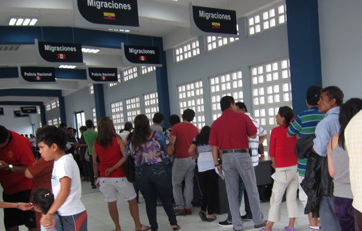 People wait in line inside the Peruvian immigration building.