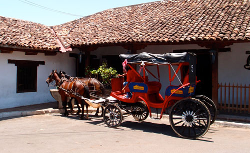 Our horse-drawn carriage parked in front of an old house in Granada.
