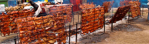 Huge racks of pork roasting on wood fires.
