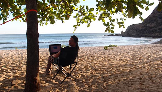 Jessica on a laptop on a beach in Nicaragua